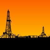 Oil rig silhouettes and orange sky Stock Image