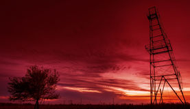 Oil rig structure and lonely tree profiled on dramatic sunset sky Stock Photography