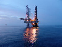 Oil rig before sunrise. Offshore oil rig in the Gulf stock image