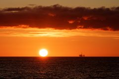 Oil rig at sunset in the north sea. The clouds uplit by the setting sun stock image