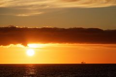 Oil rig at sunset in the north sea. The setting sun just below a bank of dark clouds over a calm sea royalty free stock photo