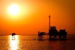 Oil rig in the sunset. Orange Stock Image