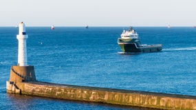 Oil rig Supply Vessel, Aberdeen, Scotland. Oil rig Supply Vessel passing by lighthouse Royalty Free Stock Photo
