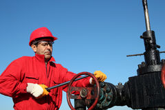 Oil Rig Valve Technician at Work. Worker in action at pump jack oil well Royalty Free Stock Photo