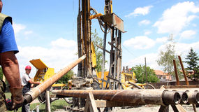 Oil Rig Workers. Oil drilling rig workers lifting drill pipe Royalty Free Stock Photo