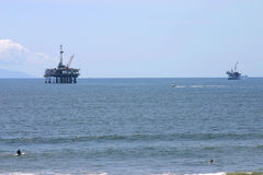 Oil rigs. Two off-shore oil rigs on the southern california coast. Surfer in the foreground Royalty Free Stock Photography