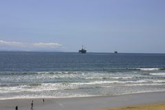 Oil rigs and beach royalty free stock photo