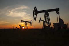 The oil pump, industrial equipment. Oil rocking at sunset in Russia, Republic of Bashkortostan stock photos
