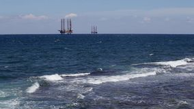 Oil rigs at sea, seen from the shore. Oil rigs in the troubled sea against a cloudy sky stock footage