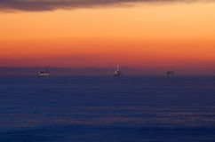 Oil rigs in sea at sunset. Illuminated oil rig platforms in sea with orange sunset background off coast of California, U.S.A royalty free stock image