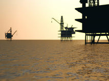Oil rigs silhouetted in sea. Scenic view of three offshore oil rig platforms silhouetted at sunset Stock Images