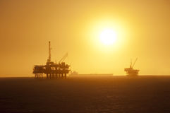 Oil rigs at sunset. Oil Rigs in the ocean, ship passing by and a beautiful sunset in Huntington Beach, California royalty free stock photography