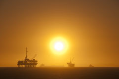 Oil rigs at sunset. Oil Rigs in the ocean, ship passing by and a beautiful sunset in Huntington Beach, California Royalty Free Stock Image