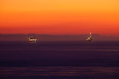 Oil rigs in sunset ocean. Scenic view of illuminated oil rigs in sea with orange sunset background off the coast of California, America royalty free stock image