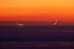 Oil rings in sea at sunset. Two illuminated oil rigs in sea with orange sunset background in Pacific ocean off the coast of California royalty free stock images