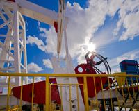 Oil rocking chairWestern Siberia. 26 August 2015 Oil  in the area of Kogalym ,Western Siberia oil wells,metallic,motor,fence,sky, clouds,Western Siberia,Russia Royalty Free Stock Photo