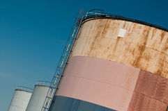Oil rusty and white tanks Royalty Free Stock Photo