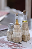 Oil, Salt And Pepper. Glass decanters of condiment oils and salt and pepper shakers, partially enclosed in white wicker holders, sitting on a table Royalty Free Stock Photography