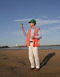 Oil sample. An environmental engineer on the mudflats examining a sample of oil from the ship docked behind him, showing the estuary and beautiful blue sky stock image