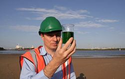 Oil sample analysis. An environmental engineer on the mudflats examining a sample of oil from the ship docked behind him, showing the estuary and beautiful blue royalty free stock photo
