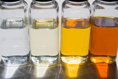 Oil samples 2. Bottles with samples of different base oils against sunlight Stock Images
