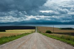 Road along the field to the sea coast royalty free stock image
