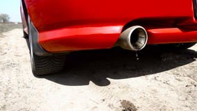 Oil and smoke flying out of the exhaust pipe of the car. Close up stock footage