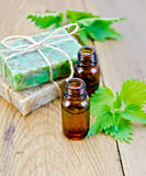 Oil and soap on board with nettle Stock Photos