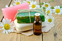 Oil with soap and camomile on board Royalty Free Stock Photos