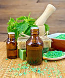 Oil and soap with nettles in mortar on board Royalty Free Stock Photos
