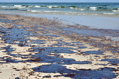 Oil Spill on Beach. With oil skimmers in background Royalty Free Stock Images