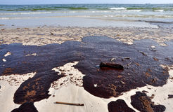 Oil Spill on Beach. With off shore oil rig in background Royalty Free Stock Photography