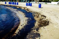 Oil spill cleanup in Agios Kosmas bay, Athens, Greece, September 14 2017. Texture of crude oil spill on sand beach from oil spill accident, Agios Kosmas bay Stock Image