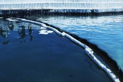 Oil spill. Environmental disaster. A containment boom is a tempo. Rary floating barrier used to contain an oil spill stock images
