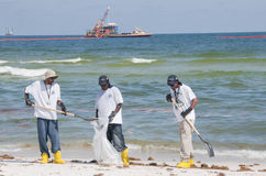 Oil spill workers at seashore royalty free stock photography