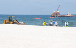 Oil spill workers at seashore Royalty Free Stock Photo