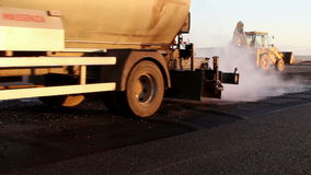 Oil spreader truck applying tack coats on a surface in preparation for paving
