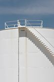 Oil storage tank details. Oil storage tank - large white tank with stairs against blue sky Royalty Free Stock Image