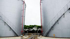Oil storage tank. Large gray open-air petroleum liquid storage tank is a good helper for storing liquid Stock Photo