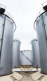 Oil storage tank. Large gray open-air petroleum liquid storage tank is a good helper for storing liquid Stock Images