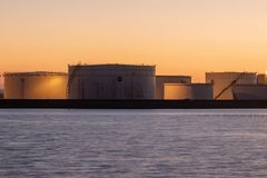 Oil storage tanks at sunset stock images
