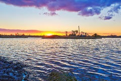The oil sucking machine lakeside sunset Royalty Free Stock Images