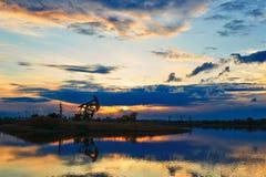 Oil sucking machine lakeside sunset Royalty Free Stock Photography