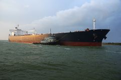 Oil Tanker in Bound. Oil tanker with tugboat is powering in bound to the harbor Royalty Free Stock Photo