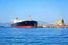 Oil tanker. Bringing its cargo in a tank storage facility Stock Image