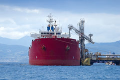 Oil tanker. Bringing its cargo in a tank storage facility Stock Images