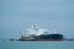 Oil-tanker at an offshore terminal. Oil-tanker unloading its cargo at an offshore oil terminal on a cloudy day. Photo taken at Sriracha harbour in Chonburi Royalty Free Stock Image