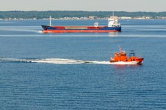 Oil Tanker and pilot boat. Copenhagen, Denmark-July 14, 2017: Container ship `Karen` heading into Copenhagen Port with a pilot boat cruising by Stock Image