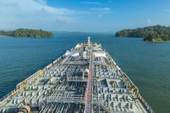 Oil tanker proceeding through Panama Canal. Oil tanker proceeding through Panama Canal by green jungle Royalty Free Stock Photo