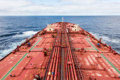 Oil tanker proceeding to cloudy skyline. Tanker deck with two green stripes Royalty Free Stock Image